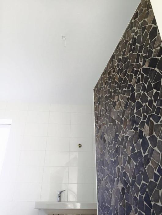 Strak wit gestuct plafond in badkamer